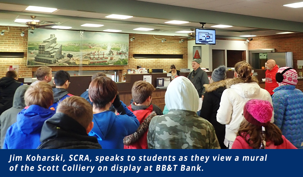 Students view a mural of the Scott Colliery