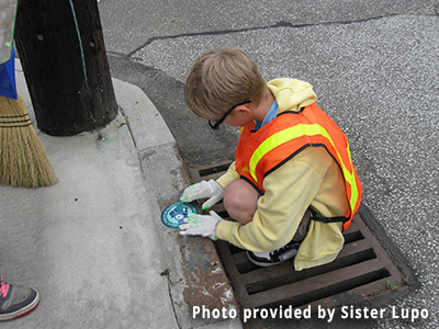 A child puts an awareness sticker on a storm drain.